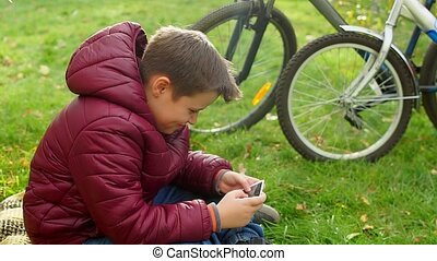 Teenage boy sitting on the grass, playing smartphone.