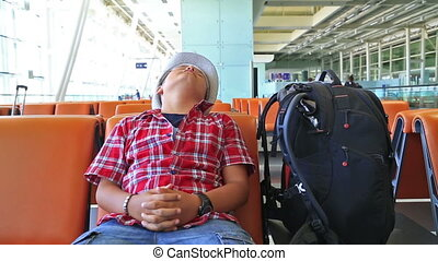 Teenage boy sleeping at the airport - Tired young boy...