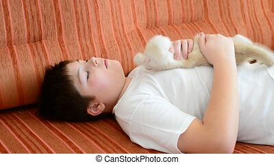 Teenage boy sleeping on couch with a kitten