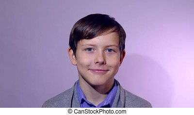 Teenage boy smiling portrait on a purple studio background
