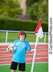 teenage boy standing at corner holding ball