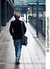Teenage Boy - Teenage boy walking away from camera in street
