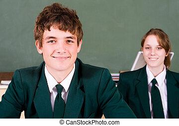 teenage boy in uniform in class