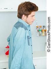 Teenage boy stood in the kitchen