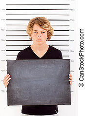 teenage boy taking criminal mug shot