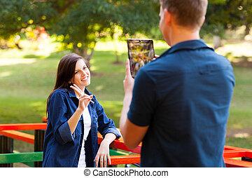 teenage boy taking picture of girlfriend