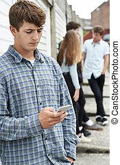 Teenage Boy Using Mobile Phone In Urban Setting