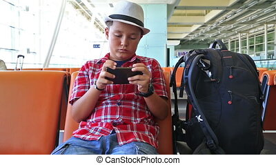 Teenage boy using smartphone at the airport