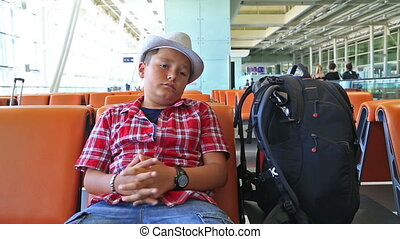 Teenage boy waiting at the airport - Tired young boy resting...