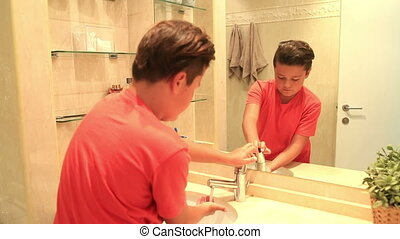 Teenage boy washing his hands
