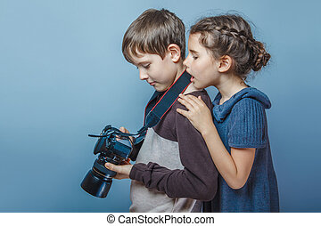 Teenage boy with a girl watching pictures on the camera on a...