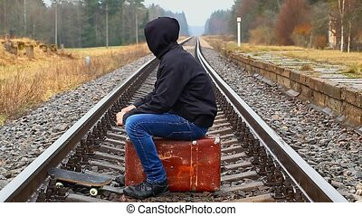 Teenage boy with a suitcase on the railway episode 2