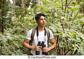 Teenage boy with binoculars hiking in forest. Summer vacation.