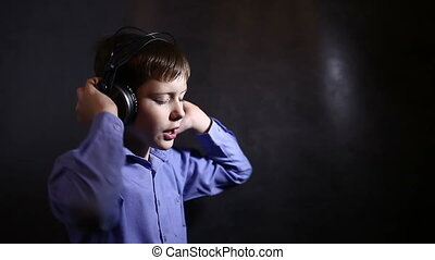 Teenage boy with headphones listening to music and sings in a blue shirt in studio on a background  of the video