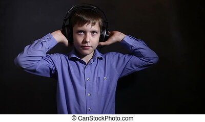Teenage boy with headphones listening to music and sings in a blue shirt in the studio on a background of the video