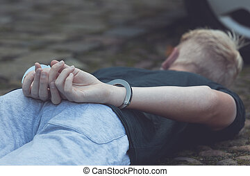 Teenage boy with his hands cuffed behind his back lying on...