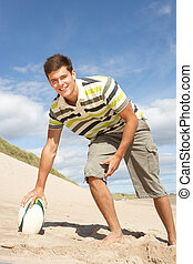 Teenage Boy With Rugby Ball On Beach
