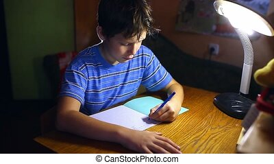teenage boy writes in notebook homework sitting at table...