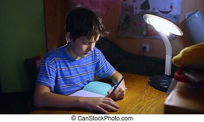 teenage boy writes in notebook homework sitting at a table...