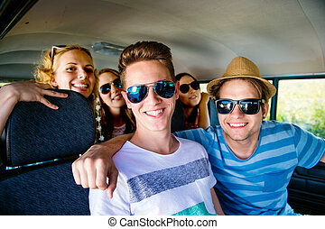 Teenage boys and girls inside an old campervan on a roadtrip, sunny summer day