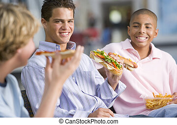 Teenage boys enjoying fast food lunches together