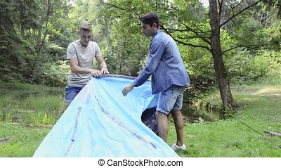 Teenage boys pitching a tent at the lake in forest. Summer...