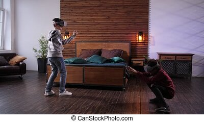 Diverse teenage friends using augmented-reality headsets and joysticks while playing video game indoors. Mixed race teenagers in futuristic VR goggles spending leisure time playing game together