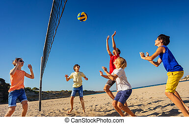 Teenage boys playing volleyball on the beach