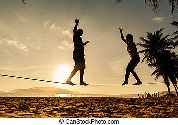 teenage couple balancing slackline on the beach - teenage ...