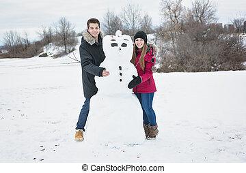 Teenage Couple Building Snowman in winter season