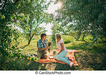teenage couple dating on picnic in green park with flowers