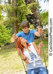 Teenage couple girl sitting on swing park