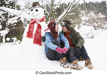 Teenage Couple In Winter Landscape Next To Snowman With Flask And Hot Drink