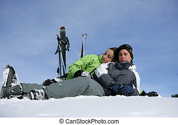 Teenage couple lying on a ski slope