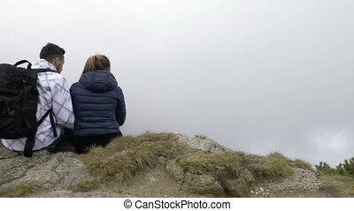 Teenage couple sitting on top of rocky mountain enjoying the view and kissing