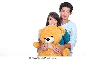 Teenage couple with a large stuffed bear