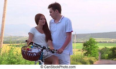 Teenage couple with bicycle and basket on country road