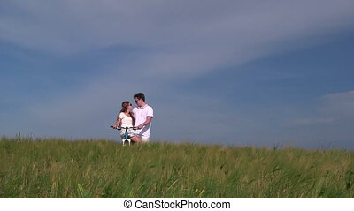 Teenage couple with bicycle in wheat field talking together,...
