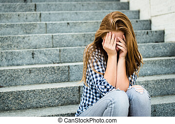 Teenage depression - Unhappy depressed teenager with face in...
