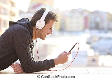 teenage dreng, lytte musik til, hos, telefon, og, hovedtelefoner