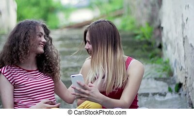 Teenage female friends sitting outdoors in town, taking...
