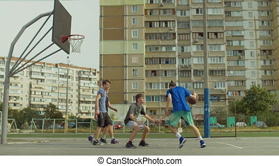 Teenage friends playing streetball on outdoor court -...