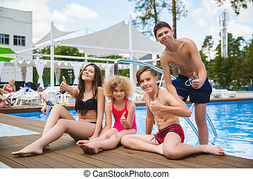 Teenage friends sitting at the edge of a swimming pool