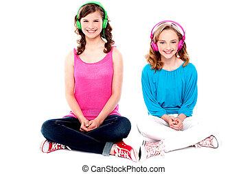 Teenage friends sitting on floor listening music