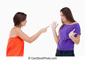 Teenage girl accusing her friend by pointing at her with her finger