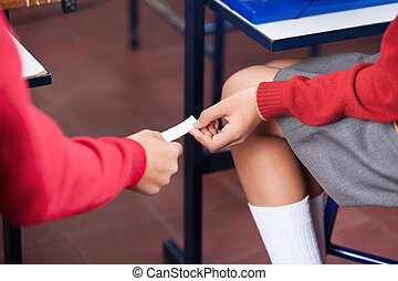 Teenage Girl And Boy Passing Cheat Sheet At Desk -...