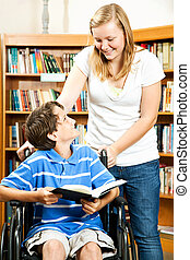 Teen girl and disabled boy in the school library.
