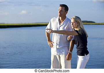 Teenage girl and father standing by water watching