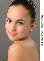 Teenage girl bare shoulders skin beauty face portrait on gray