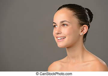 Teenage girl bare shoulders skin cosmetics beauty smiling on gray background